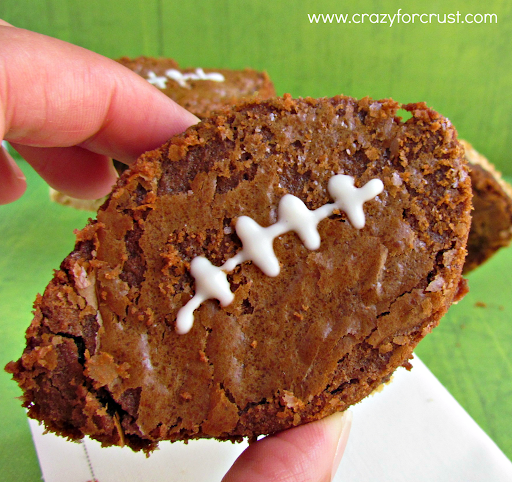 Nutella brownie football with peanut butter shortbread crust on a green background held by a woman's fingers