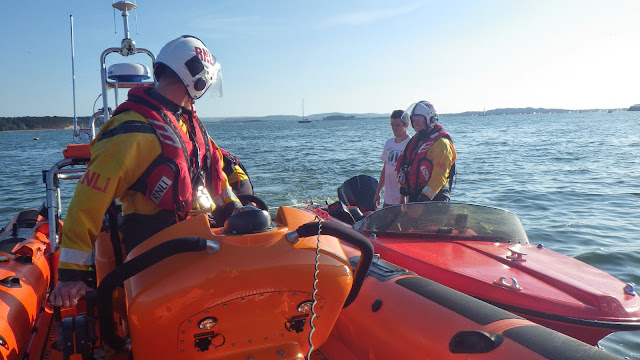 Poole ILB placing a broken down speedboat in an alongside tow after it was picked up next to Poole Lifeboat Station 12 June 2014 Photo: RNLI Poole