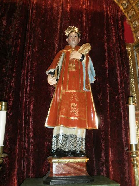 Talla de madera donde se representa al santo vestido con dalmática, sosteniendo un libro en la mano derecha y la palma del martirio en la izquierda