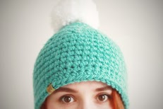 A girl with red hair wearing a Crocheted non itchy Mint colored Beanie with a white pom pom
