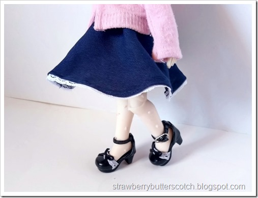 Showing off the navy blue skirt worn by the doll.  You can see her cute shoes too.