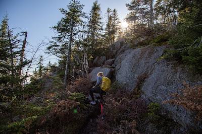 Women wearing leggings ascending rock face of mountain