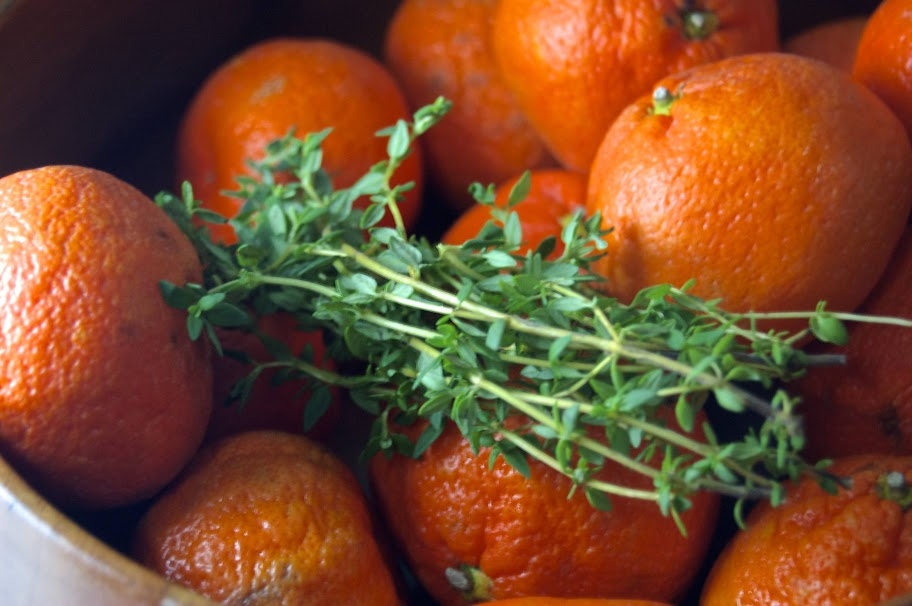 fresh satsumas and thyme in a wooden bowl
