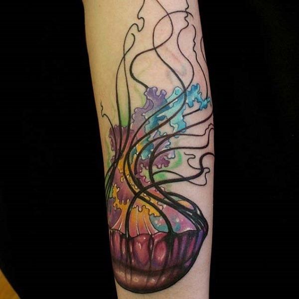 Um maravilhoso olhando água-viva tatuagem com uma trilha de cores por trás dele. a água-viva é mostrado para ser emissor de cores a partir de seus tentáculos, o que torna a olhar realmente bonito e brilhante. Os tentáculos em si são simples preto para dar mais atenção para o multicolor dentro delas.