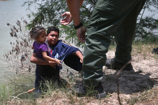 A U.S. Border Patrol agent assists undocumented minors near the U.S./Mexico border. Photo: John Moore / Getty Images