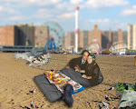 """DREAMSCAPE: Going ahead with the """"wedding,"""" John wants to snuggle with Phyllis inside the kind of quilt they slept in under the Coney Island boardwalk. A clam bake is in progress (rear), and Phyllis is wearing a wreath of flowers and her wedding band."""