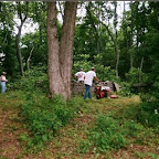 Left Virginia Melton waits to pick up brush.  2nd from left George cleans out the grave sites of Michael Gleaves.  Right :  Owen Gleaves mows with a small tractor.