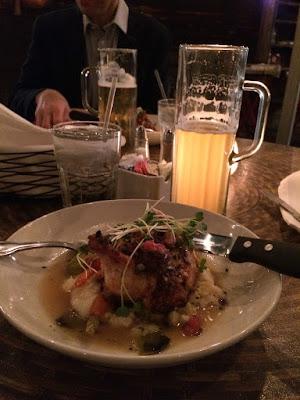 En dyp tallerken med kylling og et halvfullt glass med øl.