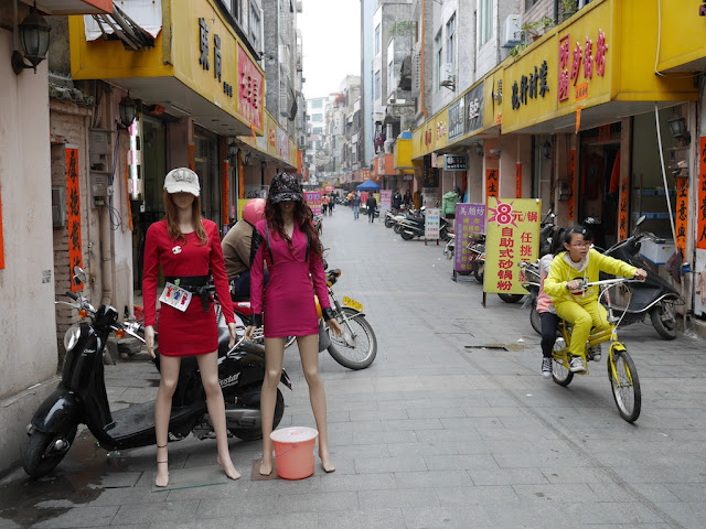 two girls on a bicycle passing mannequins in Yangjiang, China