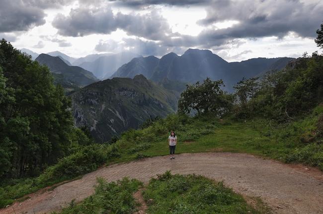 Caminante parada en el camino mirando al fotografo, en un camino de montaña, bajo un cielo abigarrado de nubes.