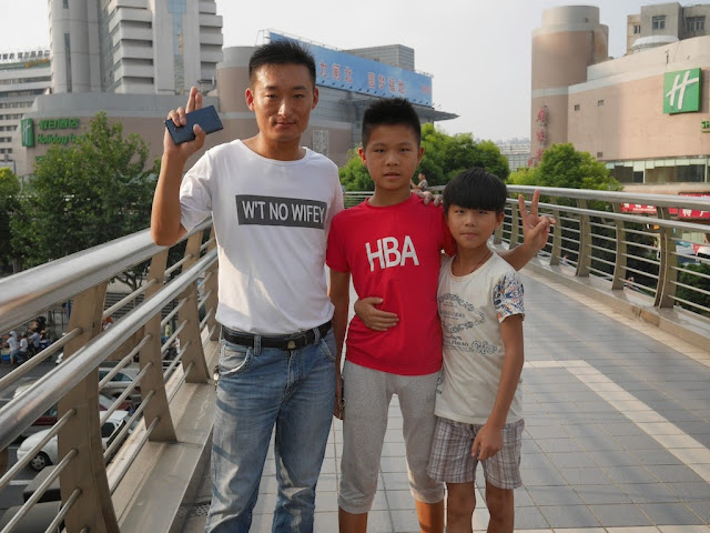 a man and two boys posing for a photograph while on a pedestrian bridge in Shanghai