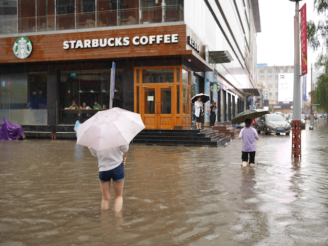 people crossing a flooded street next to a Starbucks in Taiyuan, China