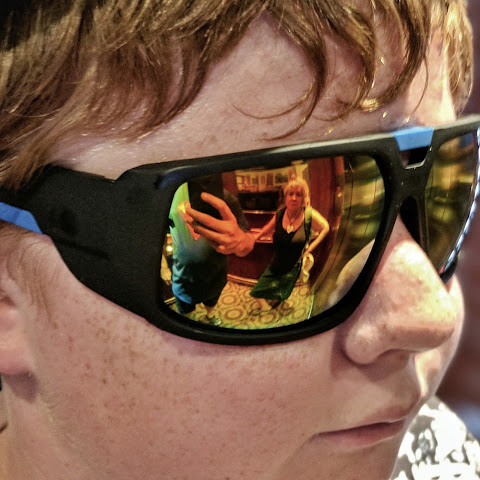 Parental reflections in a boy's sunglasses