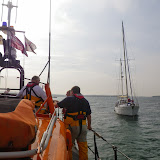 ALB crew members assist the yacht which has refloated after running aground on Stone Island - 17 September 2014.  Photo credit: Poole/RNLI