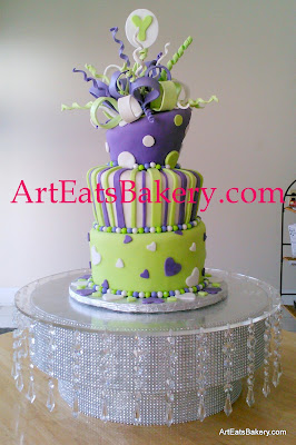 Purple, green and white mad hatter hearts, polka dots and stripes custom wedding cake design with edible bow and monogram topper on rhinestone and crystal cake stand