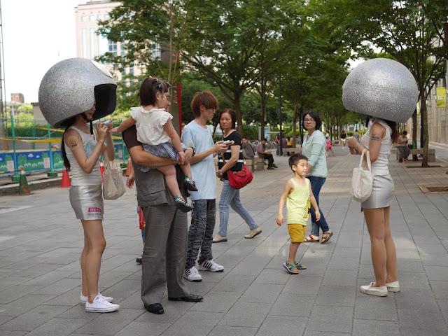 to young women wearing huge silver helmets and passersby