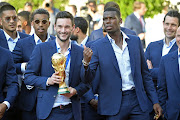 France Captain Hugo Lloris and Paul Pogba react as he holds the trophy as French President Emmanuel Macron receives the France football team during a ceremony at the Elysee Palace on July 16, 2018 in Paris, France.