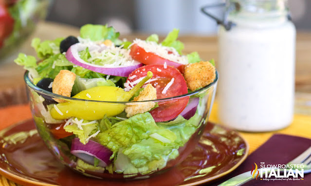 olive garden salad dressing in the background of the salad