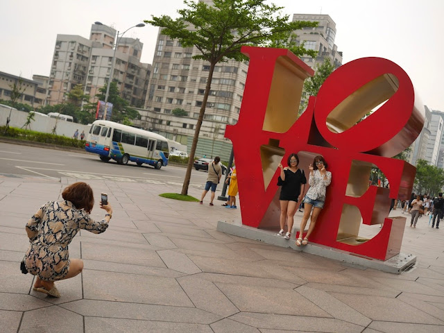"two young women having their photograph taken in front of a sculpture of Robert Indiana's ""LOVE"" design in Taipei, Taiwan"
