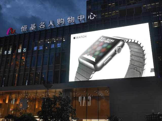 Apple Watch advertisement on large video screen above an Apple Store in Shanghai