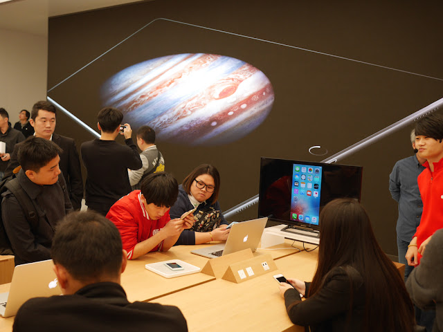customers in front of monitor displaying Jupiter at the SM Lifestyle Center Apple Store in Xiamen, China