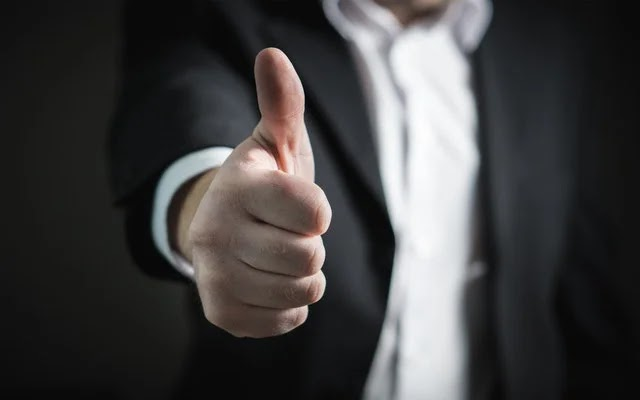 Thumbs up sign of SME owner which means the business is  successful