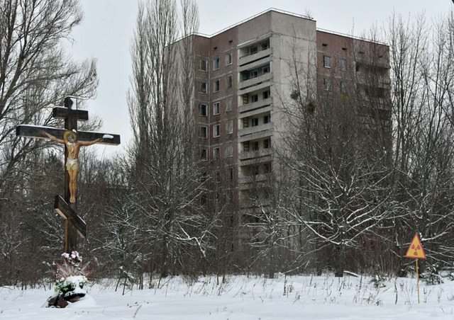 A crucifix and a radiation warning sign in front of apartment buildings in the ghost city Pripyat near to Chernobyl Power Plant, 22 January 2016. Photo: Genya Savilov / AFP / Getty Images