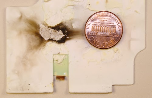 Burn marks inside an Apple Macbook charger that malfunctioned.