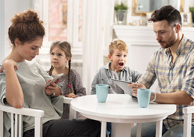 mum and dad on phones while girl looks at mum and boy looks at dad
