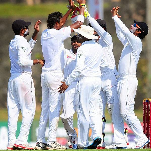 Sri Lankan cricketers celebrate after dismissing South African cricketer Dean Elgar during the first day of the opening Test match between Sri Lanka and South Africa at the Galle International Cricket Stadium in Galle on July 16, 2014.