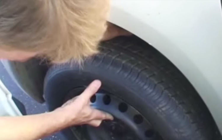 Sean Obeirne's father changing the tyre after a lion chomped it in the Kruger National Park.