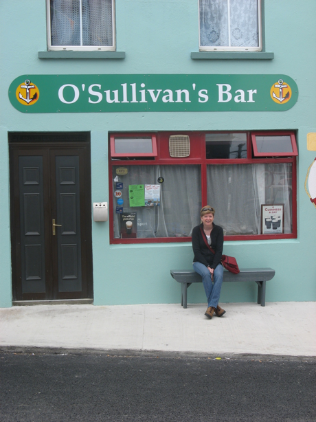woman sitting on a bench outside a pub in Ireland