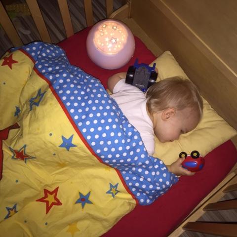 Knuddelkäfer im Bett mit Traktor und Auto im Arm