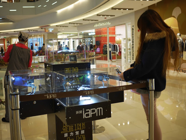 young woman photographing a small model of a Star Wars starfighter at the IAPM shopping center in Shanghai