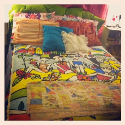 boho chicstyle bed with lots of bright colors and an Ikea fabric as bedspread