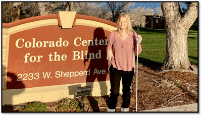 Maureen Nietfeld standing in front of the Colorado Center for the Blind sign in front of the building