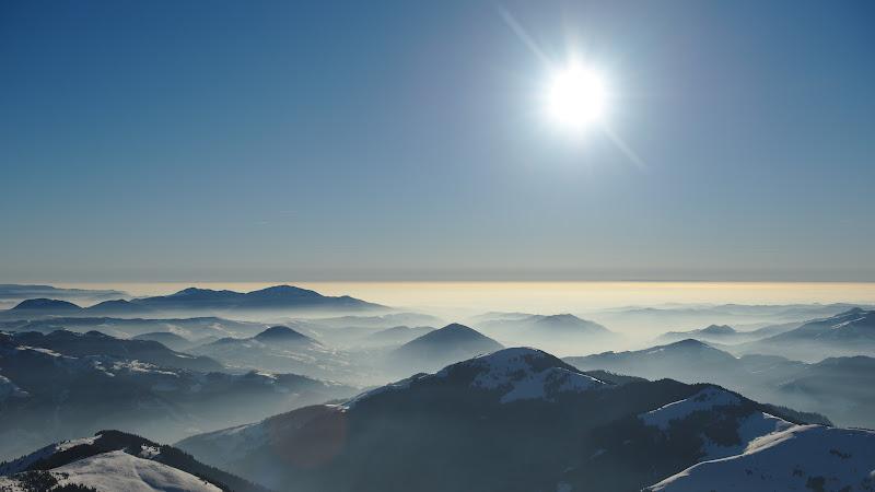 Ceata inca domneste deasupra depresiunii Transilvaniei. Deasupra in schimb, un soare orbitor.