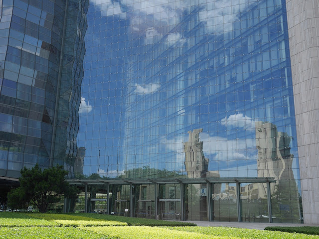 blue skies and clouds reflecting off a building at the intersection above the Dongsi Shitiao metro station in Beijing