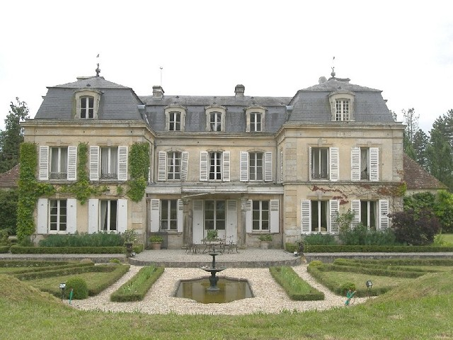 large manor home with formal gardens in front