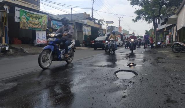 Jalan berlubang dan dipenuhi genangan air hujan di Raya Kalirungkut Kota Surabaya pada Senin