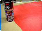 Spray a large piece of red paper with spray adhesive.