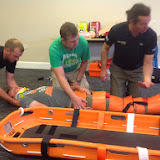 Moelfre (Gaz), Poole (Scott) and Clovelly (Steve) crew members preparing to log roll Joe into a basket stretcher - July 2014 Photo: Dave Riley