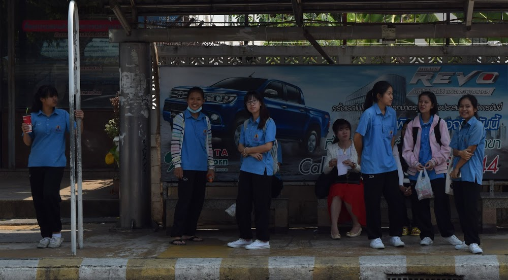 Schoolgirls wait the next songthaew outside the Wittayayon University in Khon Kaen.