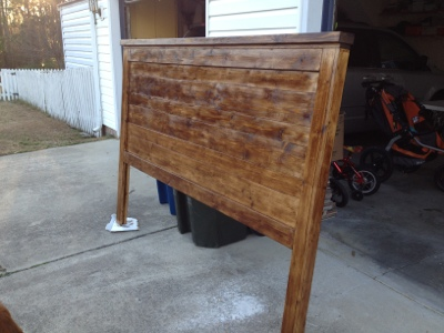 An in progress picture of a wood headboard after staining a dark walnut color