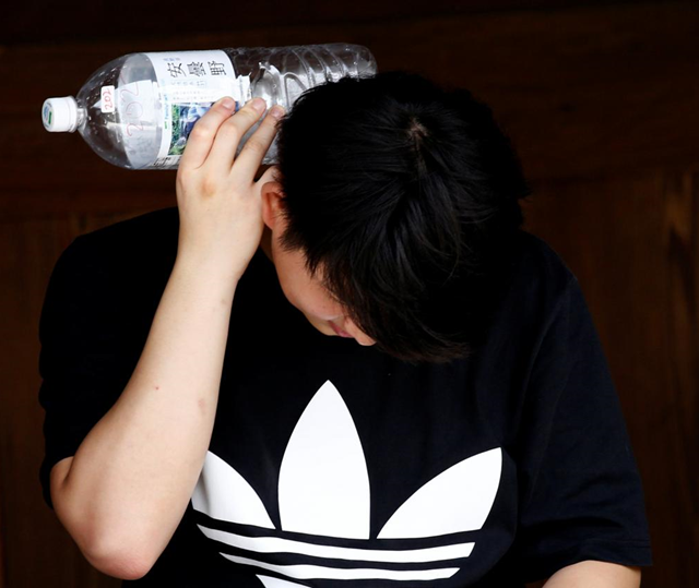 A man cools himself down with water in a plastic bottle at Meiji Shrine during a heatwave in Tokyo, Japan, 25 July 2018. Photo: Kim Kyung-Hoon / REUTERS