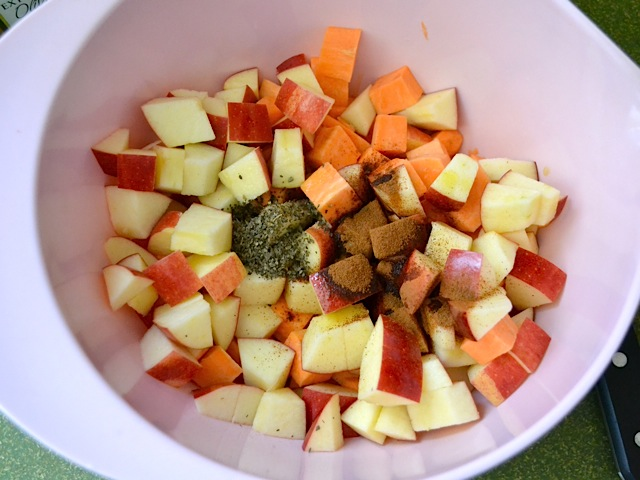 cubed apples and sweet potato with seasoning added in mixing bowl