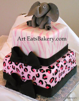 Square animal print pink, black and white zebra and cheetah fondant baby shower cake design with bows and 3D elepant topper