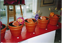 13 flowerpots, filled with earth, each has a Yoni made out of clay put on it and a rose, painted with window -colours ona  foil
