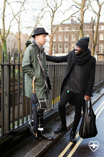 John Jarrett; stylist; Uniqlo hat; Uniqlo jumper; Topman trousers; Stutter Heim coat; Ted Baker brolly; Comme des Garcon folio; Oliver Sweeny boots;Charley Van Purpz; designer; Topman jumper; Topman jeans; 75 snood; 75 bag; Oliver Sweeney shoes; 30W hat; American Apparel glasses;