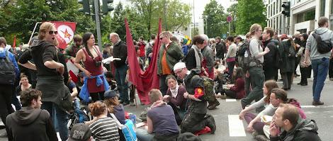Demonstranten, stehend und sitzend mit Fahnen und Transparenten.